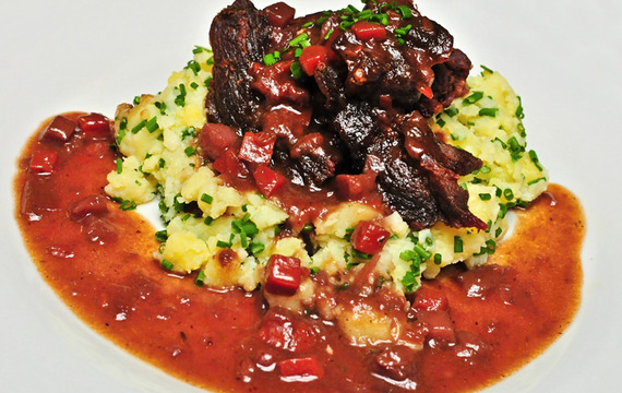 Jehněčí kýta ve šťouchaných pažitkových bramborech, přelitá omáčkou z kořenové zeleniny