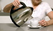 Span2.stock-footage-woman-pouring-hot-water-from-kettle-into-cup-in-slow-motion